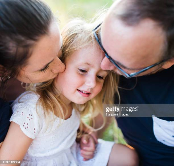 A midsection of young father and mother kissing a toddler daughter outdoors in nature in summer.