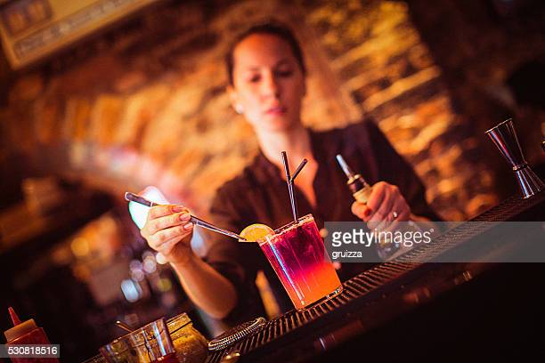 Midsection of young female bartender preparing cocktail in cocktail bar