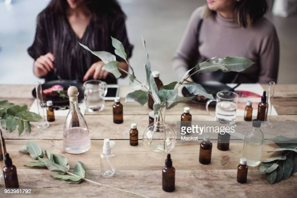 midsection of young female colleagues sitting at table with various perfume bottles in workshop - olores agradables fotografías e imágenes de stock