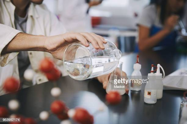 midsection of young male student pouring liquid solution in flask on table at laboratory - chemistry stock pictures, royalty-free photos & images