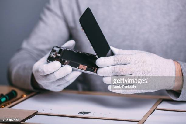 Midsection of young male technician repairing smart phone at electronics store