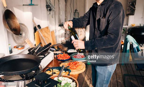 midsection of young man holding olive oil bottle in kitchen - mid section stock photos and pictures