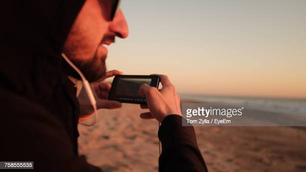 midsection of young man in hooded shirt photographing with mobile phone at beach during sunset - mensagem com foto imagens e fotografias de stock