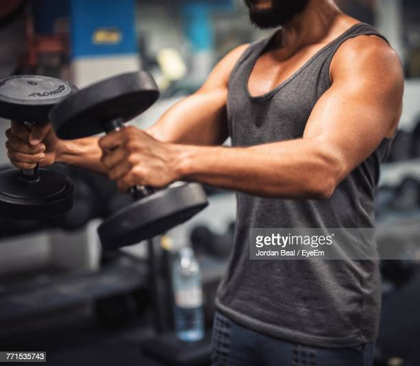 midsection of young man lifting dumbbell in gym - haltere - fotografias e filmes do acervo