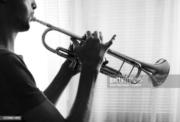 midsection of young man playing trumpet while standing at home - tromba foto e immagini stock