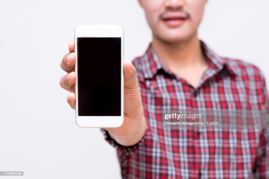 Midsection Of Young Man Showing Mobile Phone While Standing Against White Background : Stock Photo