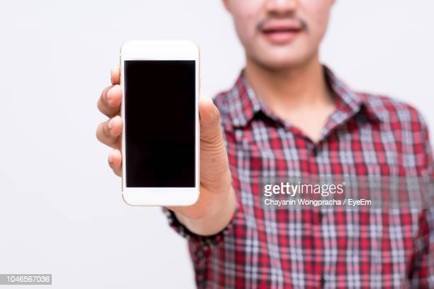 midsection of young man showing mobile phone while standing against white background - tonen stockfoto's en -beelden