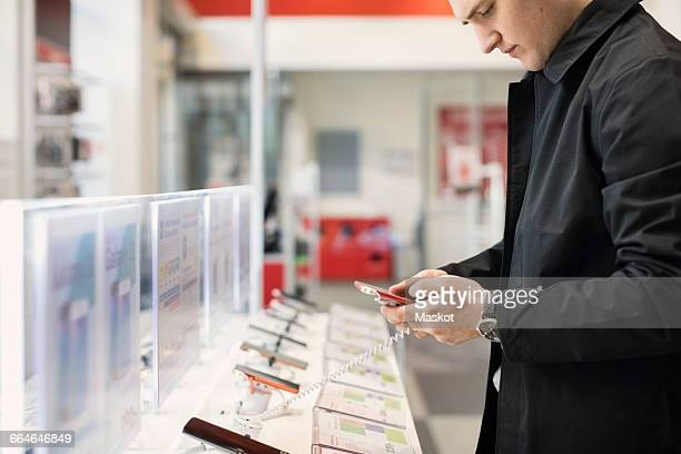 Midsection of young man using smart phone at store