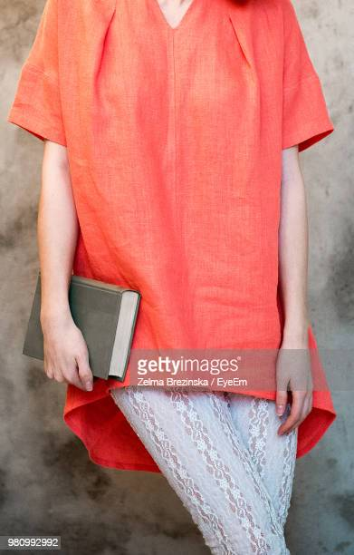Midsection Of Young Woman Holding Book While Standing By Wall