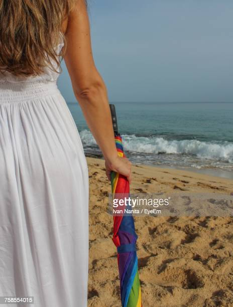Midsection Of Young Woman Holding Colorful Umbrella While Standing At Beach During Sunny Day