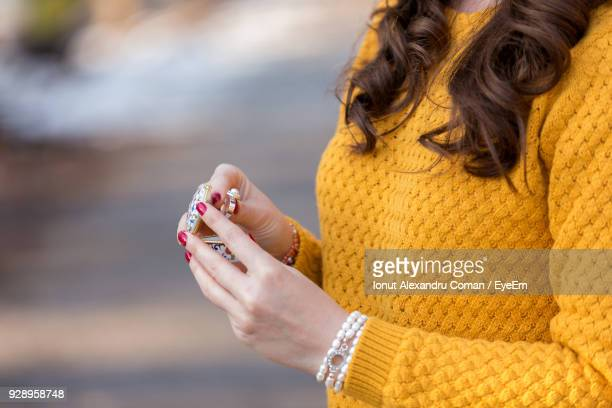 Midsection Of Young Woman Holding Ring