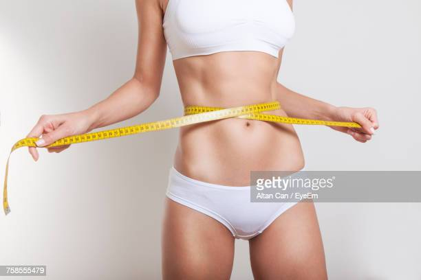 Midsection Of Young Woman Measuring Abdomen Against White Background