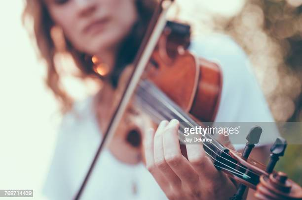Midsection of young woman playing violin