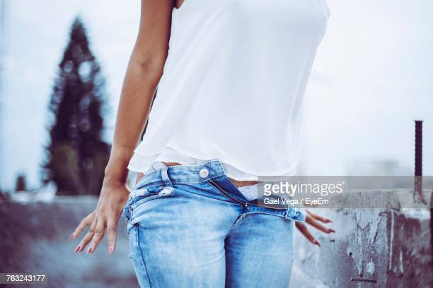 Midsection Of Young Woman Removing Jeans While Standing Outdoors