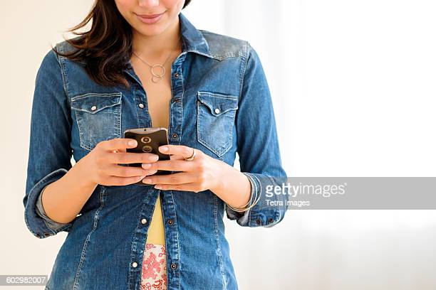 Mid-section of young woman texting