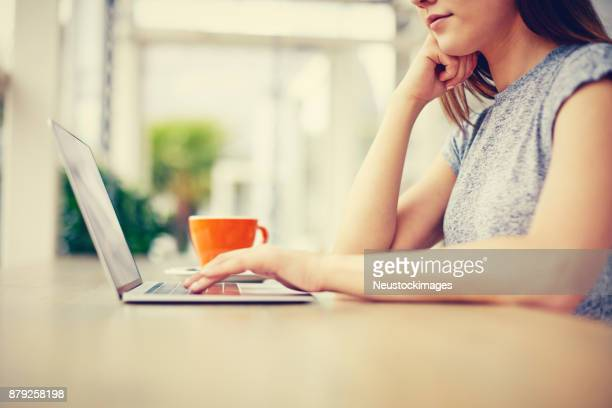 Midsection of young woman using laptop at table in cafe