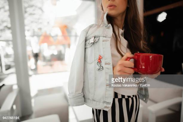 midsection of young woman with coffee standing in restaurant - red jacket stock pictures, royalty-free photos & images