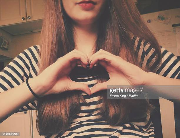 Midsection Of Young Woman With Long Brown Hair Making Heart Shape With Hands While At Home