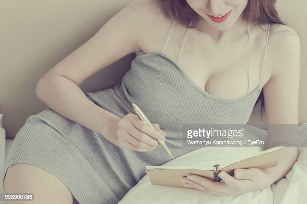 midsection of young woman writing on book while resting in bedroom - cleavage close up stock photos and pictures