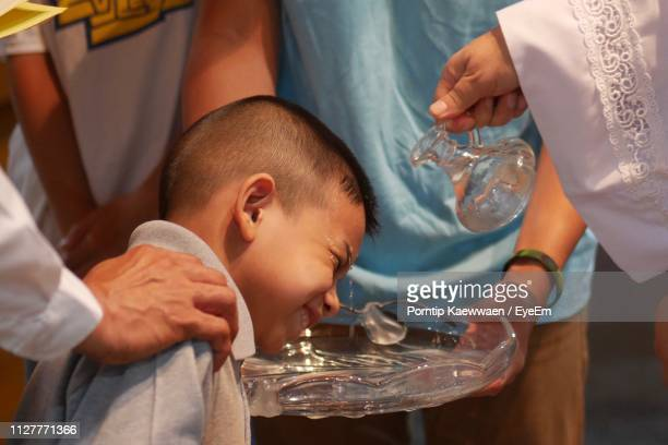 midsection pastor giving baptism to boy in church - catholic baptism stock pictures, royalty-free photos & images