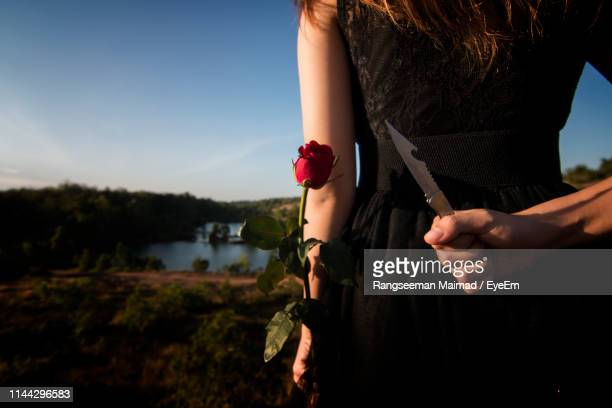 midsection rear view of woman holding knife and rose behind her back on land - hands behind back stock pictures, royalty-free photos & images