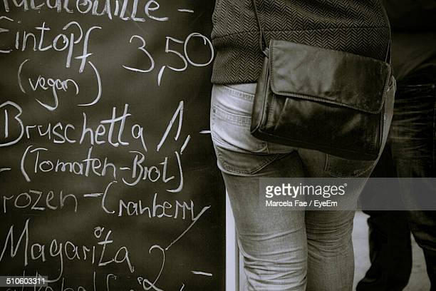Midsection rear view of woman standing by menu board