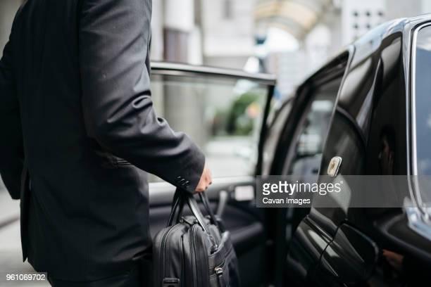 midsection side view of businessman entering taxi on city street - bolsa preta - fotografias e filmes do acervo