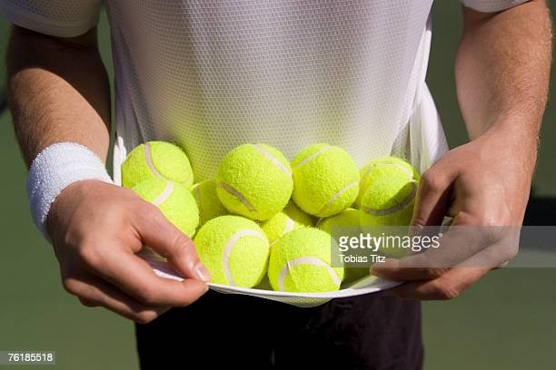 Midsection view of a man carrying tennis balls in his t-shirt