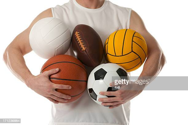 Midsection view of a man holding sports balls
