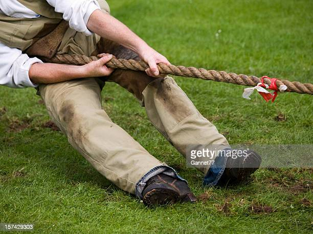 Midsection view of a man pulling a rope in a tug-of-war.