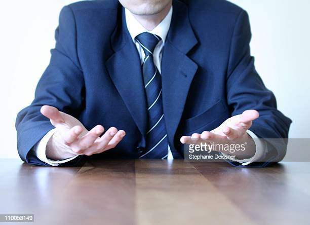 Midsection view of businessman sitting at table in office