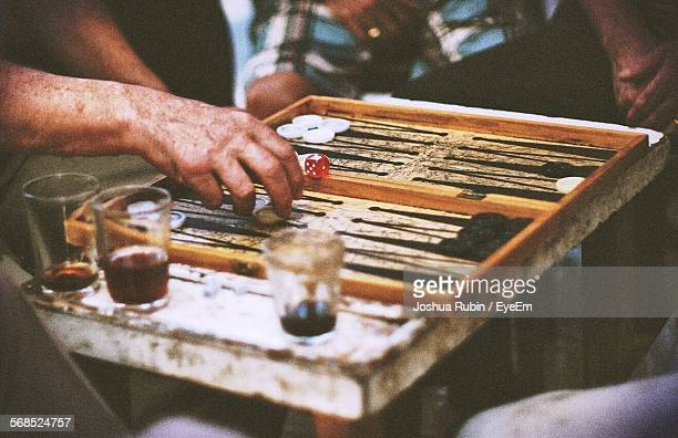 midsection view of men playing backgammon - backgammon stock pictures, royalty-free photos & images