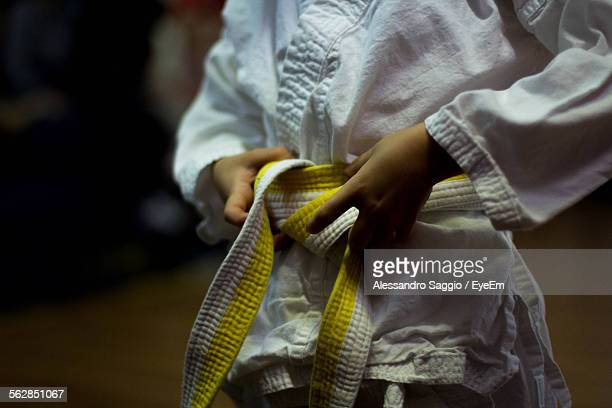 midsection view of person tying karate belt - martial arts stock photos and pictures
