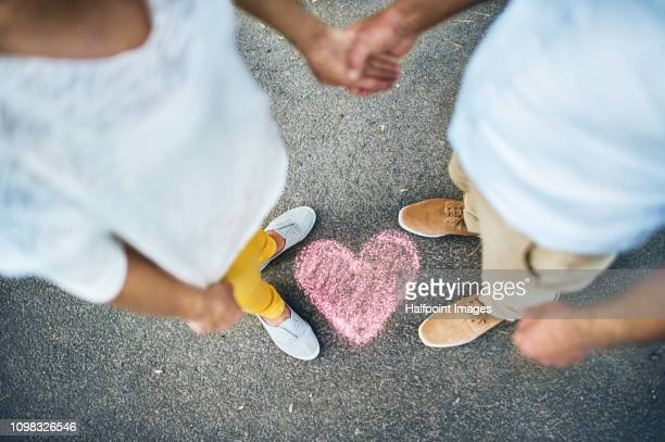 a midsection view of senior couple standing on a road, with chalk heart by their feet. - old man feet stock pictures, royalty-free photos & images