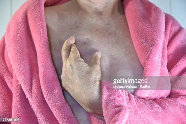 Midsection Woman Wearing Pink Bathrobe With Fingers Crossed