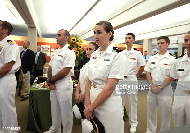 Midshipman first class Evan Roth by the flowers with hands crossed midshipmen third class Catherine Brown to the right of Roth and Catherine Philbin...