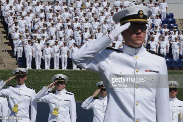 Midshipmen salute as they listen to the national anthem during a graduation ceremony at the US Naval Academy May 24 2019 in Annapolis Maryland The...