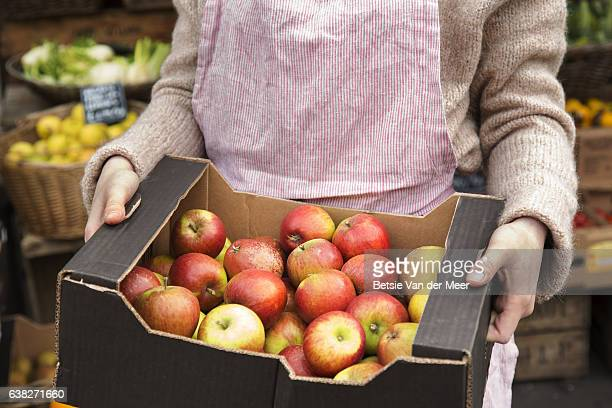 Midshot of shop assistant holding crate with organic apples in organic produce shop.