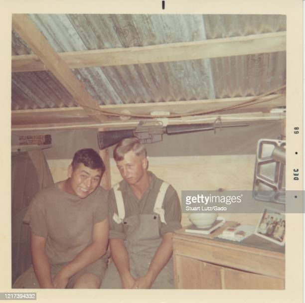 Mid-shot of two servicemen, one smiling at the camera and the other looking off-frame, sitting together in a cramped wooden barrack with a corrugated...