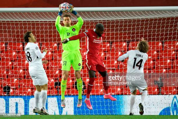 Midtjylland's Danish goalkeeper Mikkel Andersen catches the ball during the UEFA Champions league Group D football match between Liverpool and...