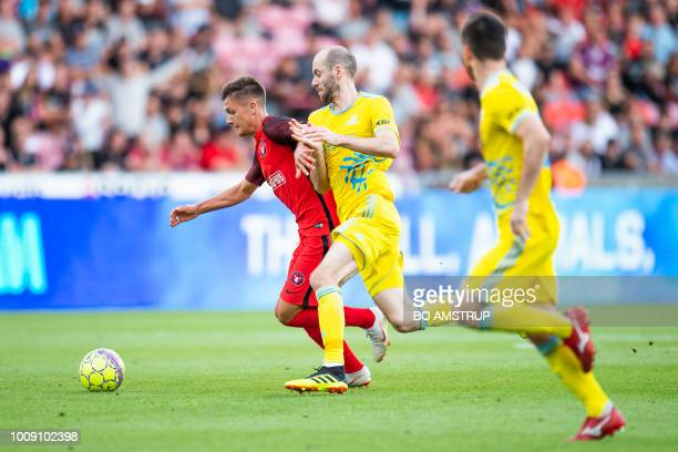Midtjylland's Mikkel Duelund and Astana's Ivan Mayewski vie for the ball during the UEFA Champions League second round second leg qualifying football...