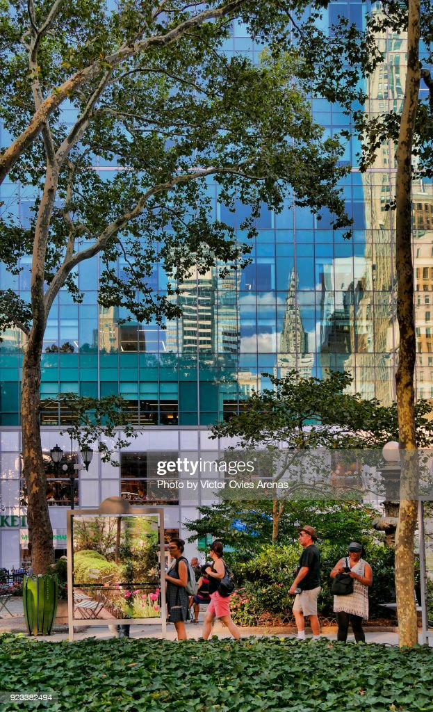 Midtown Manhattan iconic buildings reflected on the glass surface of the skyscrapers on 6th Avenue in front of Bryant Park, New York, USA : Foto de stock