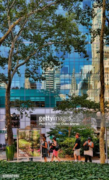 midtown manhattan iconic buildings reflected on the glass surface of the skyscrapers on 6th avenue in front of bryant park, new york, usa - victor ovies fotografías e imágenes de stock