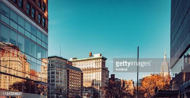 midtown manhattan skyline with distant view of empire state building - 商業不動産 ストックフォトと画像