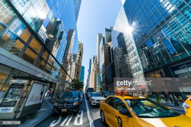 midtown manhattan traffics go through among the illuminated manhattan skyscrapers on 42nd street at manhattan new york city usa on jul. 30 2017. rows of buildings stand along the street, which reflect buildings to their windows each other. - jul photos et images de collection