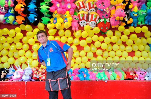 Midway worker Caleb Hileman looks on from his stand at the 199th Topsfield Fair in Topsfield Massachusetts on September 29 2017 The Topsfield Fair is...