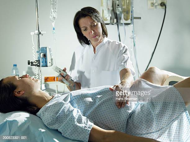 Midwife checking woman's pregnancy in hospital