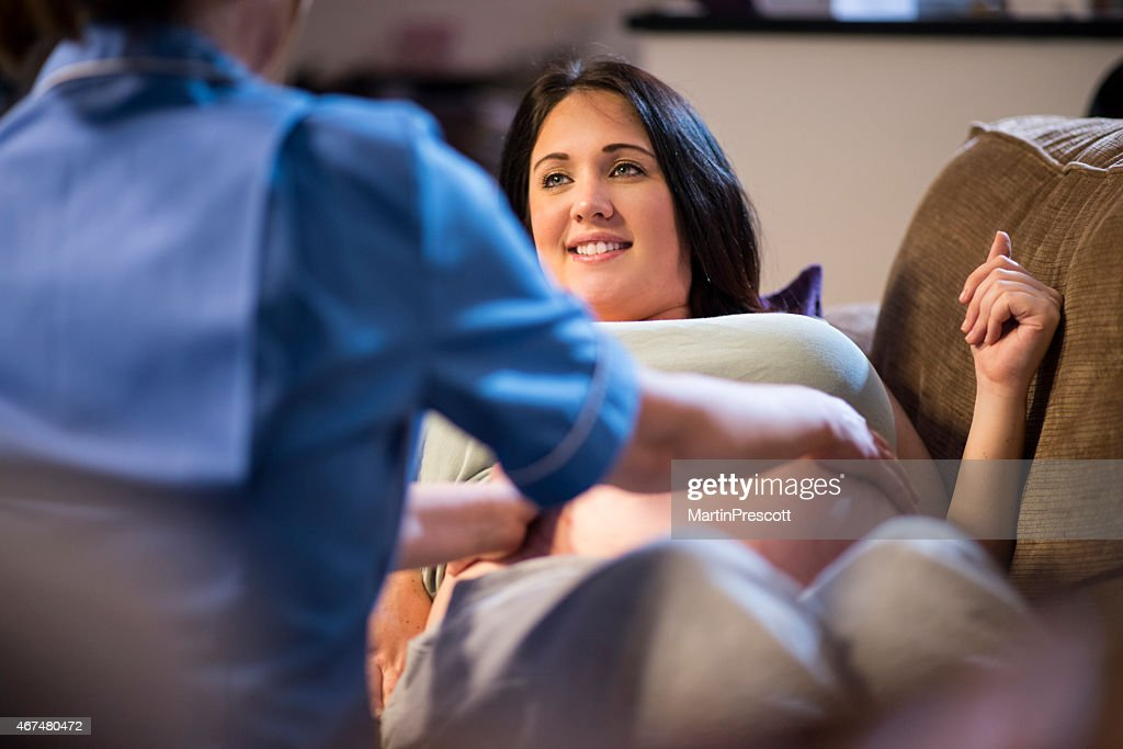 Midwife examining pregnant patients abdomen during home visit : Stock Photo