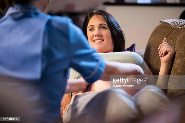 Sage-femme examiner enceinte en visite chez les patients de l'abdomen