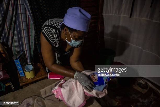 Midwife Ivy Gatsi wraps a newborn baby girl in blankets before handing the her to the infant's mother for the first time in the early hours of the...